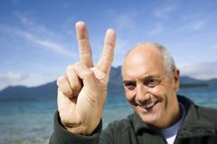 Germany, Bavaria, Walchensee, Senior man showing victory sign - stock photo