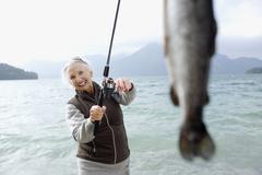 Germany, Bavaria, Walchsensee, Senior woman fishing in lake - stock photo