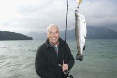 Germany, Bavaria, Walchensee, Senior man fishing in lake - stock photo