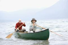 Germany, Bavaria, Walchensee, Senior couple rowing boat on lake Stock Photos
