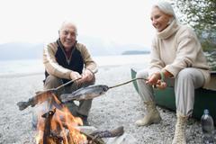 Germany, Bavaria, Walchensee, Senior couple sitting at campfire, grilling fish - stock photo