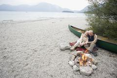 Germany, Bavaria, Walchensee, Senior couple sitting at campfire - stock photo