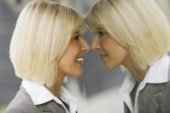 Germany, businesswoman smiling, looking at mirror reflection - stock photo