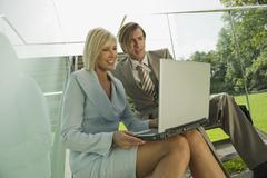 Germany, two business people using  laptop - stock photo