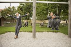Germany, business people sitting on swings in playground Stock Photos