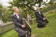 Germany, business people riding rocking horses  in playground Stock Photos
