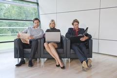 Germany, business people sitting in lounge, working Stock Photos