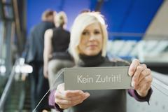 Germany, businesswoman holding prohibition sign, - stock photo
