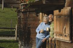 Austria, Karwedel, Senior couple leaning on log cabin, holding mugs - stock photo