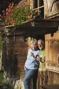 Austria, Karwendel, Senior couple leaning on log cabin, holding mugs - stock photo
