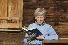 Austria, Senior woman reading book, sitting at log cabin - stock photo