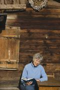 Austria, Senior woman reading book by log cabin - stock photo
