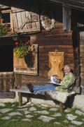 Austria, Karwendel, Senior man sitting in front of log cabin, reading a book - stock photo