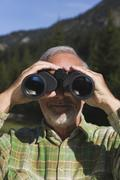 Austria, Karwendel, Senior man looking through binocular, portrait - stock photo
