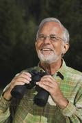 Austria, Karwendel, Senior man holding binocular, portrait - stock photo