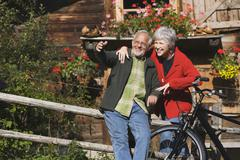 Austria, Karwendel, Senior couple in front of log cabin - stock photo