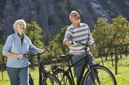 Stock Photo of Austria, Karwendel, Ahornboden, Senior couple pushing bikes