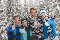 Stock Photo of Italy, South Tyrol, Young people in winter clothes,  thumbs up, portrait