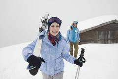Italy, South Tyrol, Young couple, woman carrying skis over shoulder - stock photo