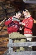 Italy, South Tyrol, Seiseralm, Couple standing on deck of log cabin, holding Stock Photos