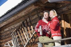 Italy, South Tyrol, Seiseralm, Couple standing on deck of log cabin, holding - stock photo