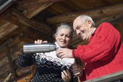 Italy, South Tyrol, Seiseralm, Senior couple standing on balcony of log cabin, - stock photo