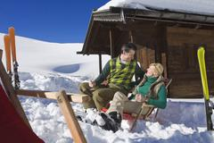 Italy, South Tyrol, Seiseralm, Couple sitting in front of log cabin, holding - stock photo
