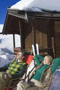 Italy, South Tyrol, Seiseralm, Couple resting in chairs by log cabin - stock photo