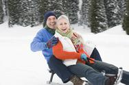 Stock Photo of Italy, South Tyrol, Seiseralm,   Senior couple sledding down hill, laughing,