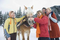 Italy, South Tyrol, Seiseralm, Family standing by horse, smiling, portrait Stock Photos