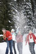 Italy, South Tyrol, Seiseralm, Four persons throwing snow in the air - stock photo
