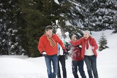 Italy, South Tyrol, Seiseralm, Four persons throwing snow in the air Stock Photos
