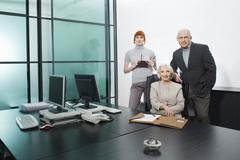 Stock Photo of Germany, Munich, Business people in office, smiling, portrait