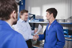 Germany, Neukirch, Apprentice and instructor shaking hands, side view Stock Photos