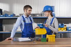 Germany, Neukirch, Young woman and foreman at workstation Stock Photos