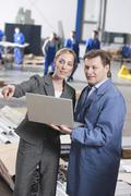 Stock Photo of Germany, Neukirch, Female architect and foreman in industrial hall