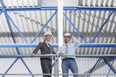 Germany, Neukirch, Man and woman architect standing in industrial hall, low Stock Photos