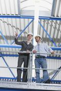 Germany, Neukirch, Man and female architect standing in industrial hall Stock Photos