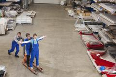Germany, Neukirch, Instructor and apprentices in industrial hall, fooling about, Stock Photos