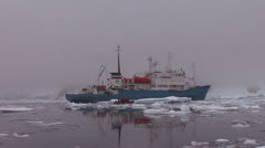An oceanic research vessel floats amongst icebergs in Antarctica. Stock Footage