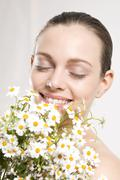 Young woman holding bunch of flowers, eyes cloes, portrait - stock photo