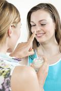 Stock Photo of Woman putting cream onto girl friends nose, portrait