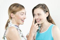 Stock Photo of Woman putting cream on girl friends nose, smiling, portrait