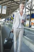 Germany, Leipzig-Halle, Airport, Young woman with suitcase on travelator Stock Photos