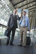 Stock Photo of Germany, Leipzig-Halle, Airport, Two businessmen on travelator, one unsing