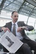 Germany, Leipzig, Businessman in Airport departure lounge, holding newspaper Kuvituskuvat