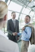 Stock Photo of Germany, Leipzig-Halle, Airport, Business people shaking hands, smiling