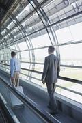 Germany, Leipzig-Halle, Airport, Two business people on travelator, rear view - stock photo