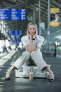 Germany, Leipzig-Halle, Young woman in Airport departure lounge, sitting on Kuvituskuvat