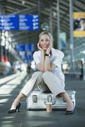 Germany, Leipzig-Halle, Young woman in Airport departure lounge, sitting on - stock photo